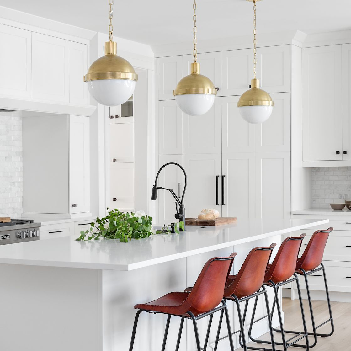 A white kitchen with vibrant red barstools