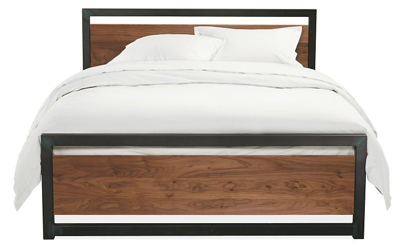 A bed with a natural steel frame and walnut head and footboards.