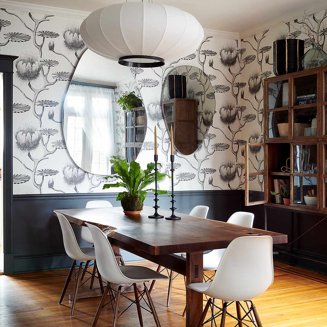 Moody dining room featuring oval mirror wall decor