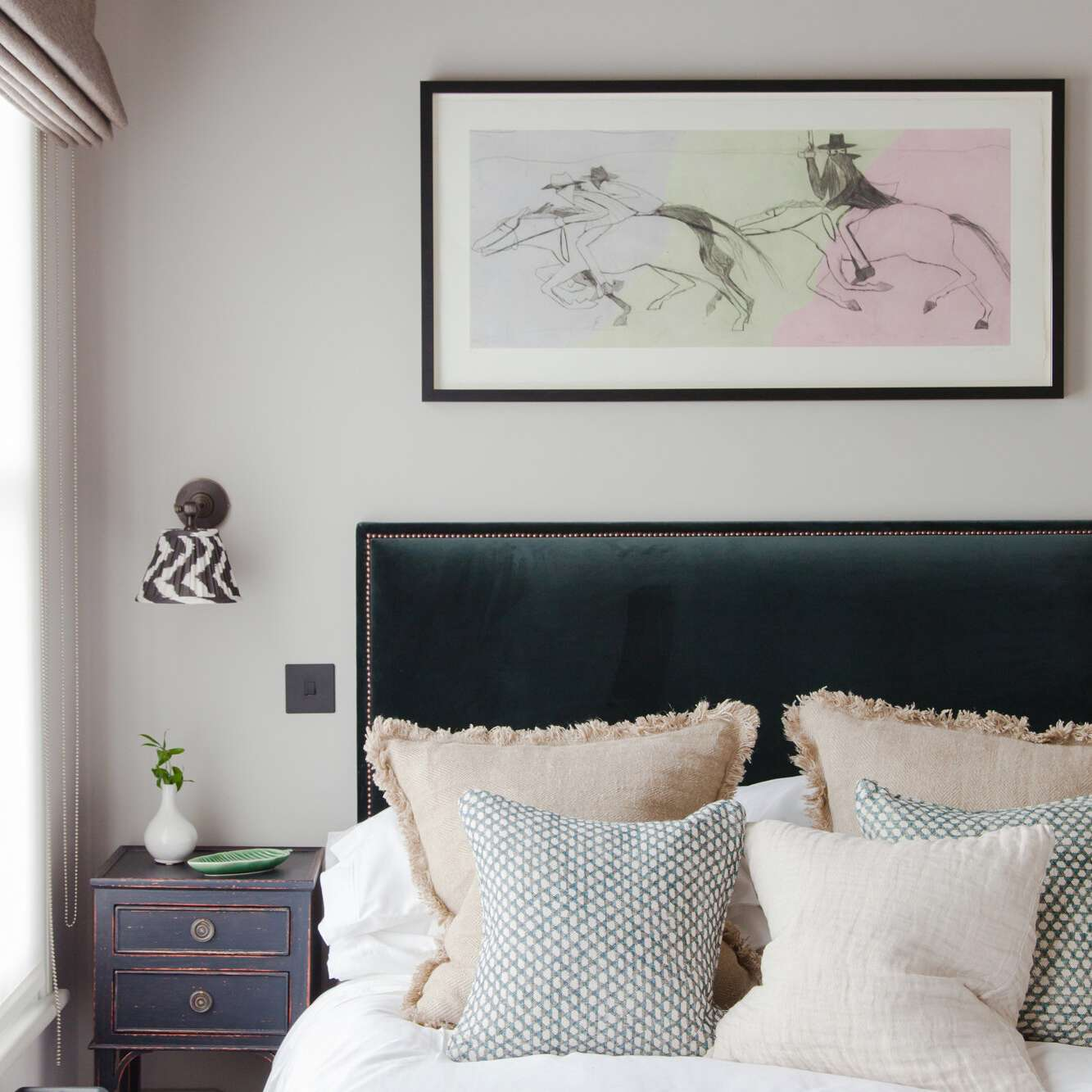 A bedroom with an indigo nightstand and a matching indigo blanket