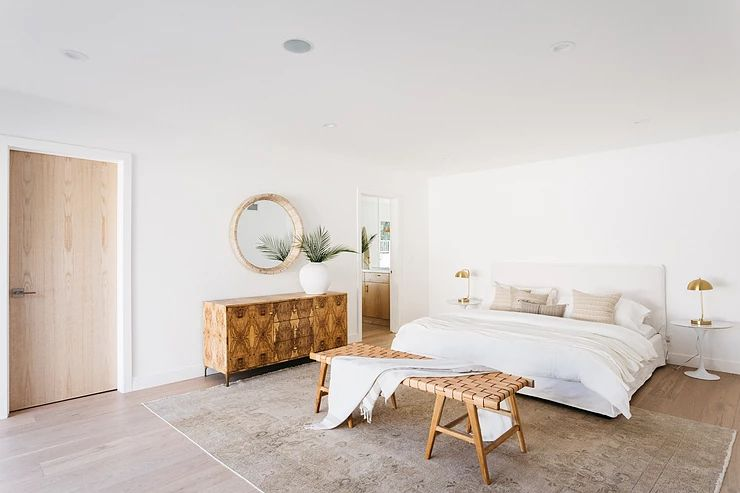 Beachy neutral bedroom with bench at foot of bed.