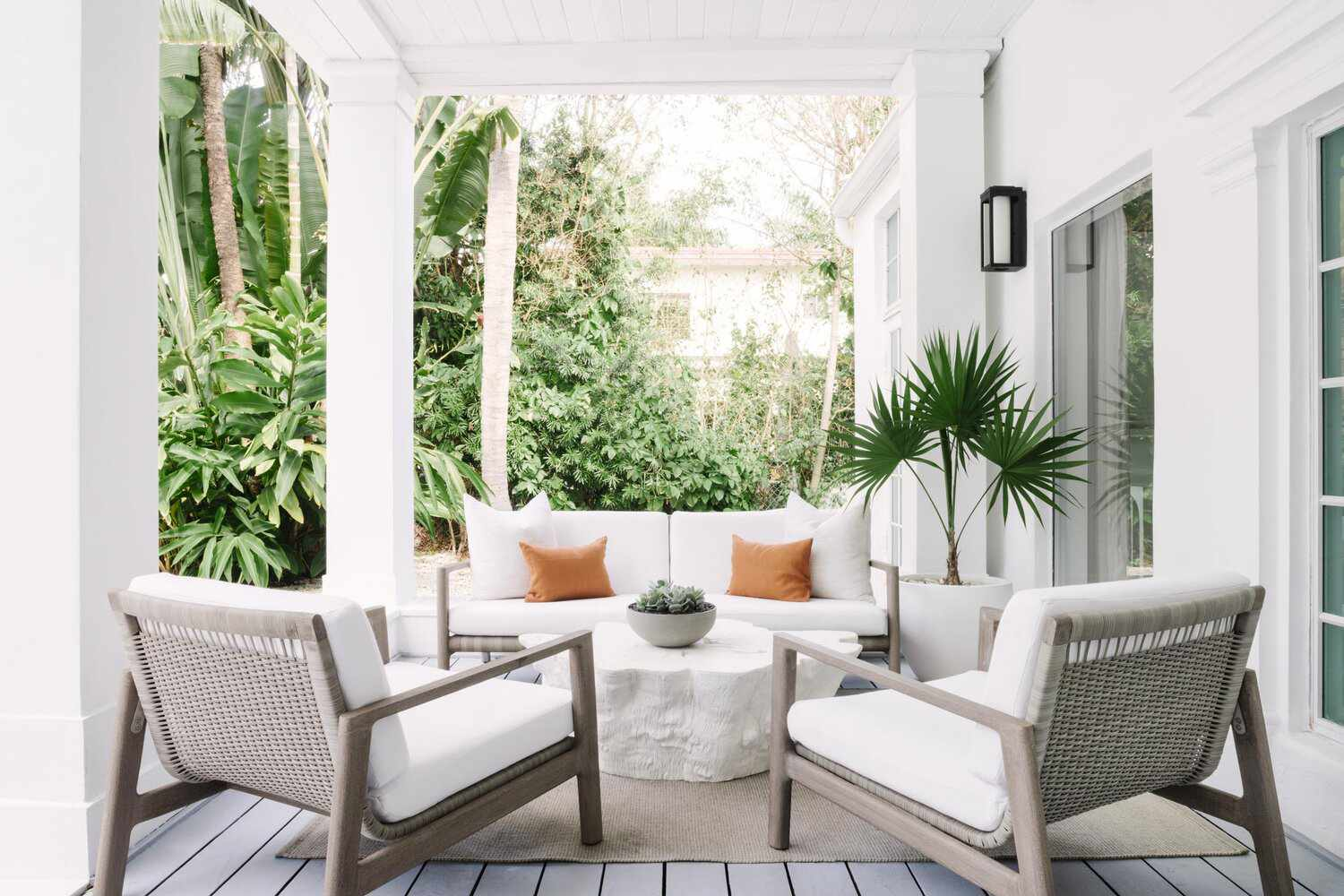 Tropical outdoor space with white sofa and orange throw pillows.