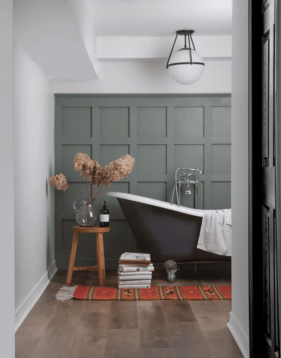 A small bathroom with a striking sage green accent wall, a clawfoot tub, and a red rug
