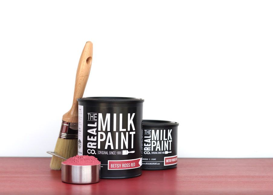A two cans of milk paint sitting side by side on a pink surface.