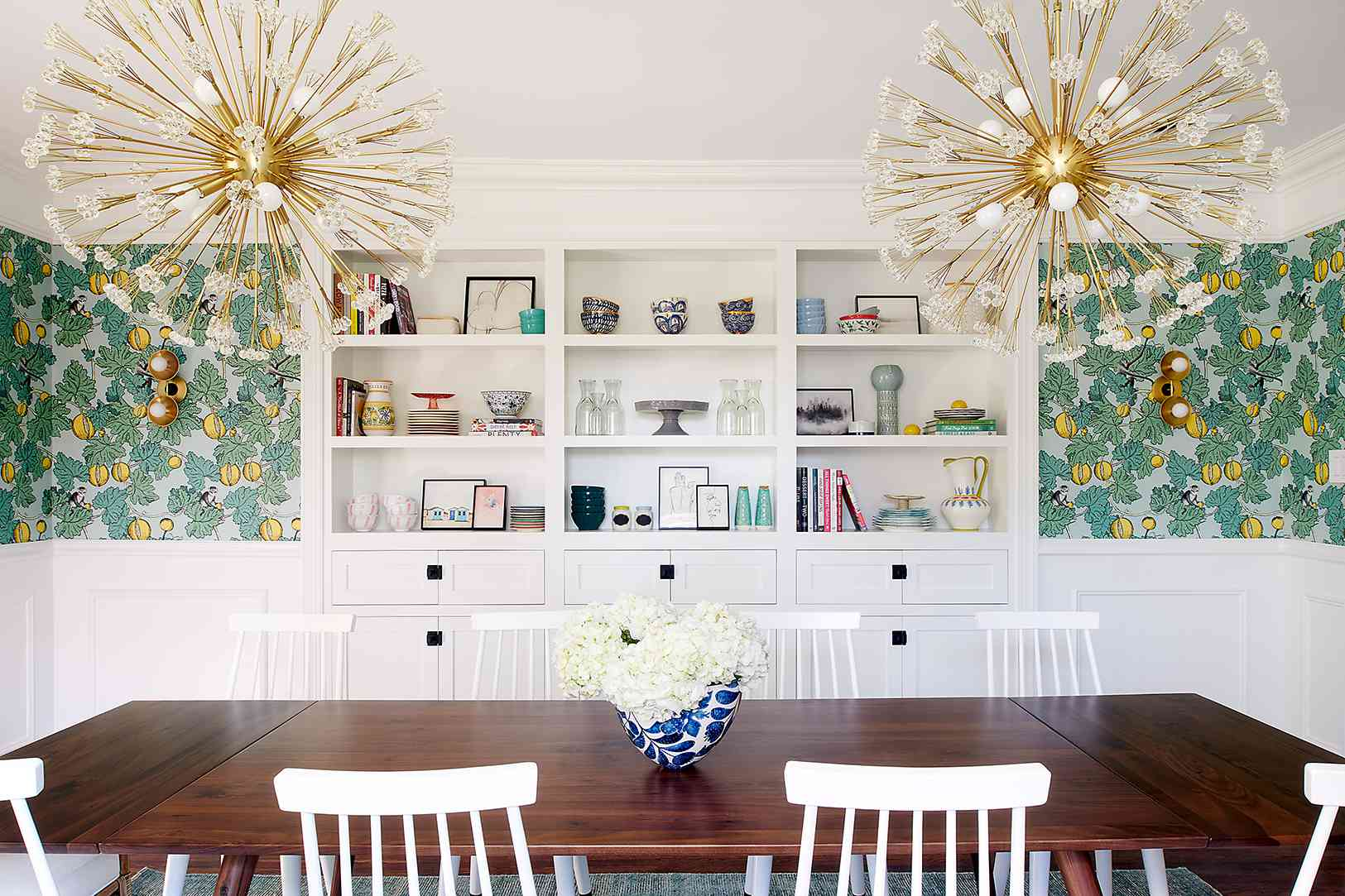 Dining room with bright wallpaper and orb lighting.