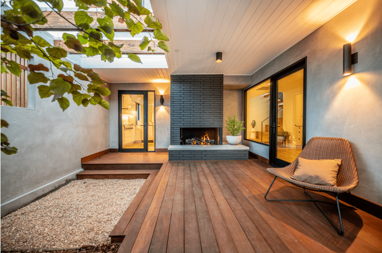 A wood-lined patio, adorned with a black brick-lined fireplace