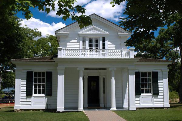 A white Greek Revival house under a blue sky