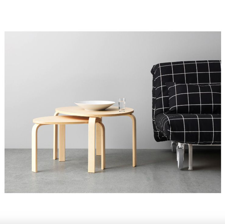 A set of two round and oval nesting tables beside a futon.
