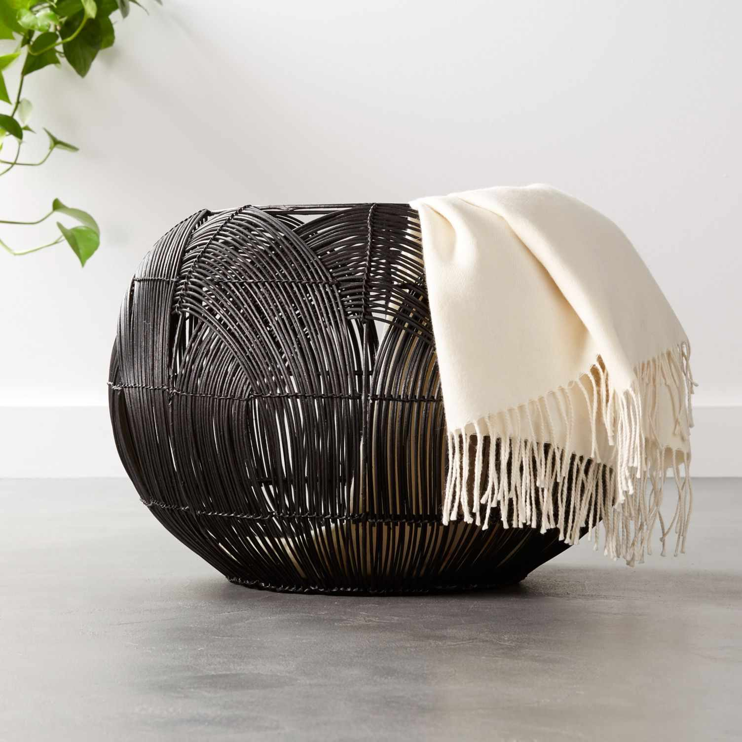 A round black woven rattan basket with a blanket draped over the side.