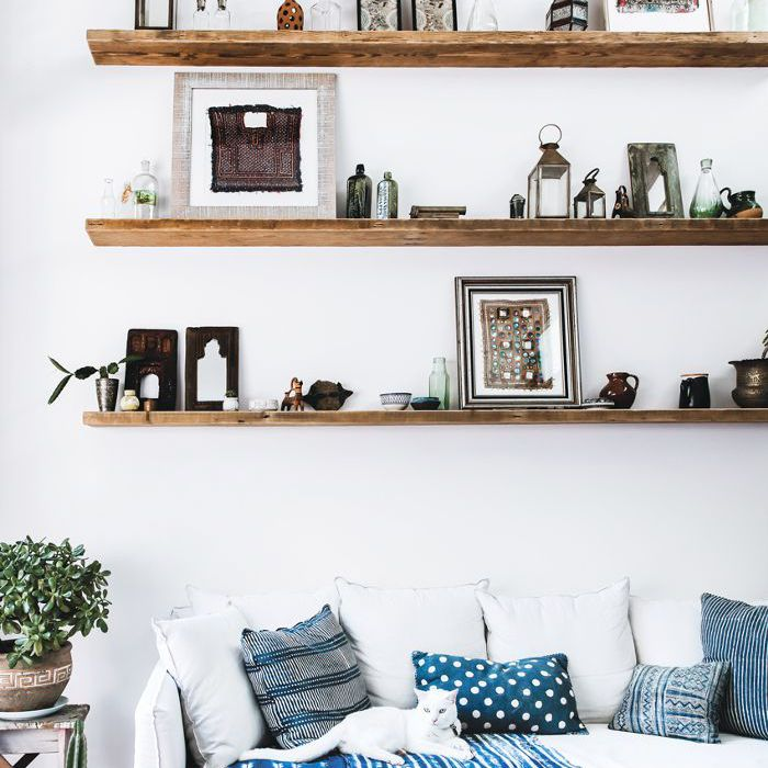 Una sala de estar decorada con capas de textiles azules y blancos.