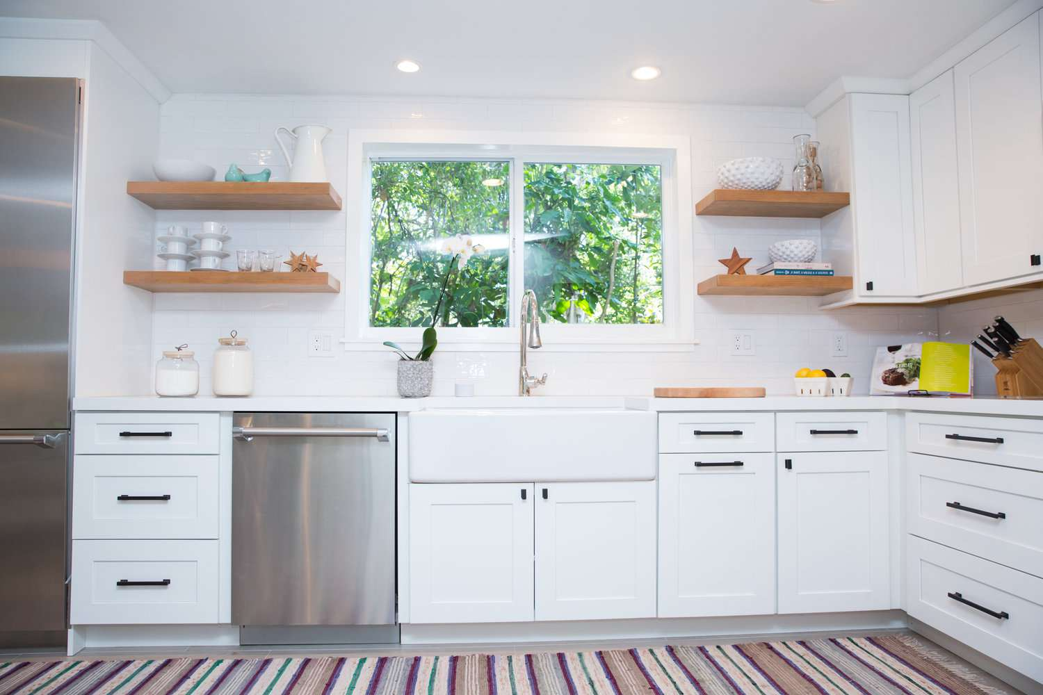 White kitchen with open shelving and stainless steel dishwasher.