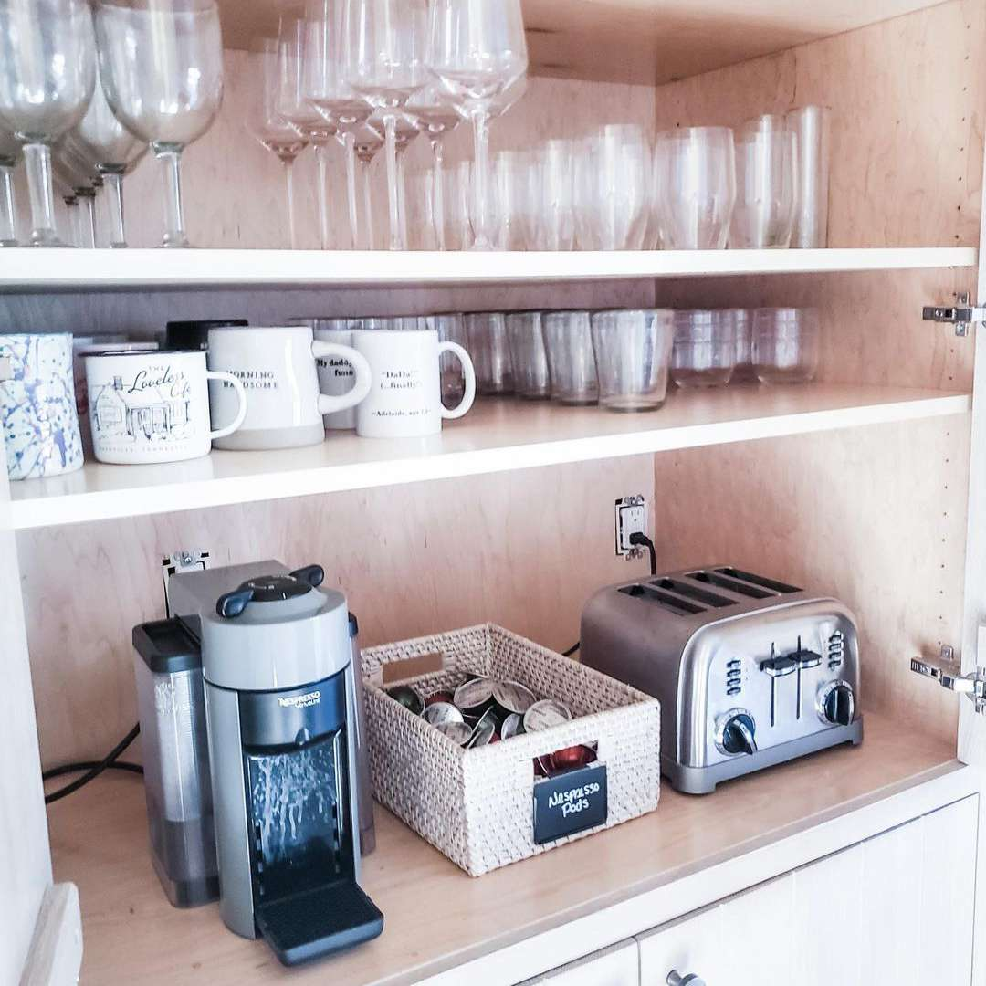 Kitchen cabinet with wine glasses and toaster