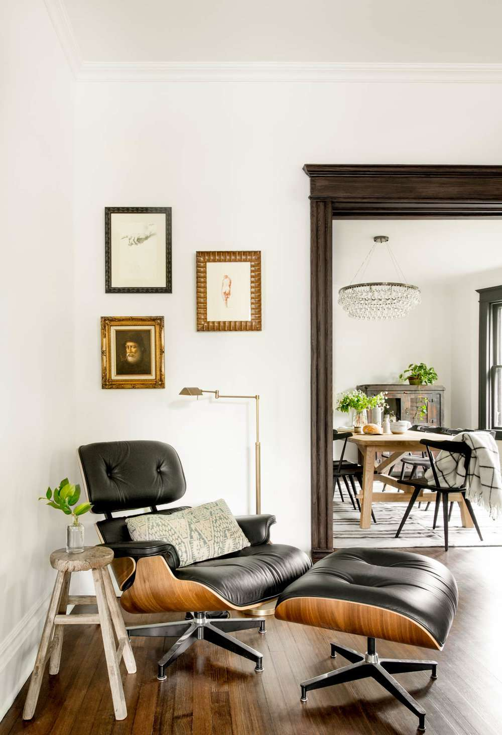Eames chair in a living room corner with assorted art hanging above