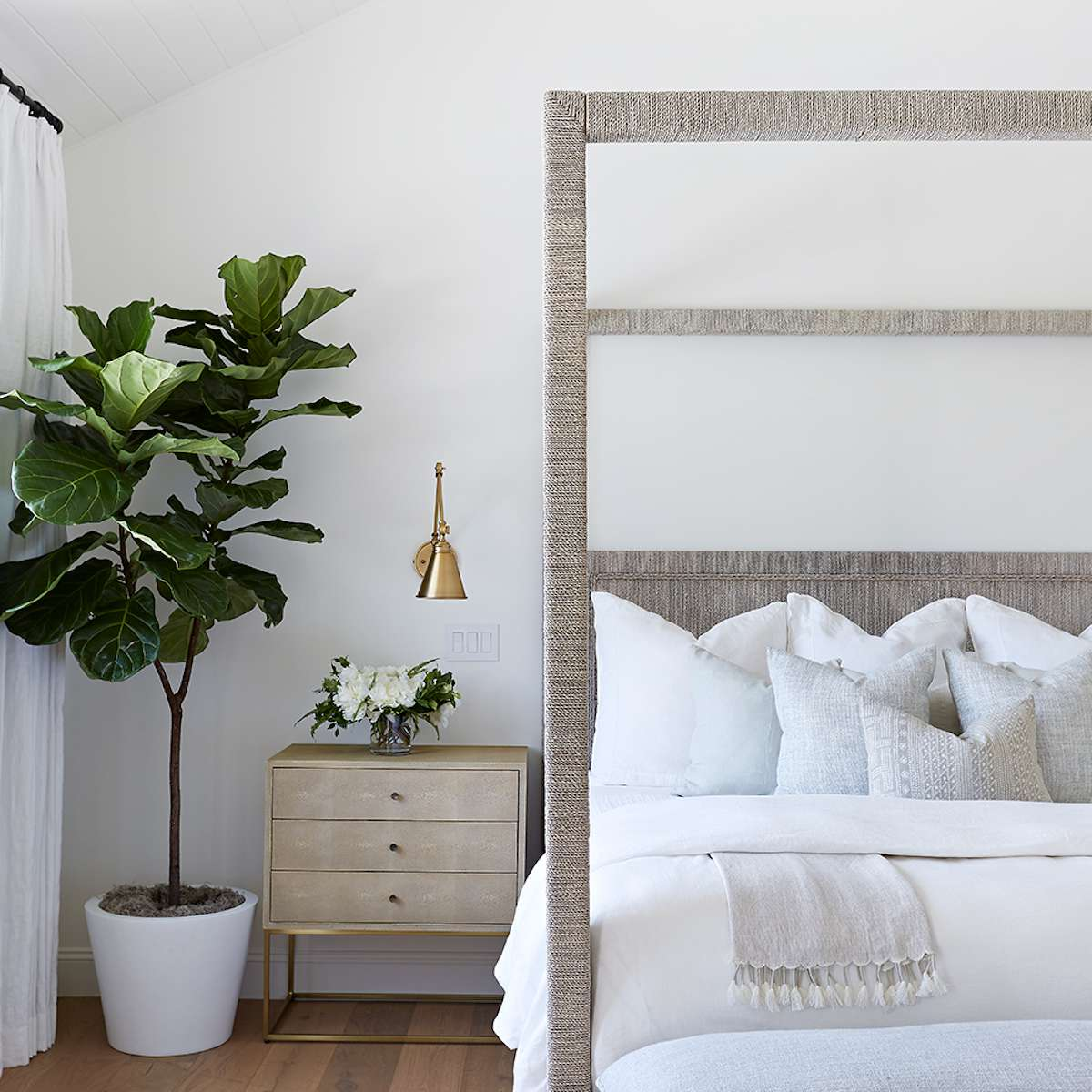 A minimalist bedroom with a woven canopy bed frame