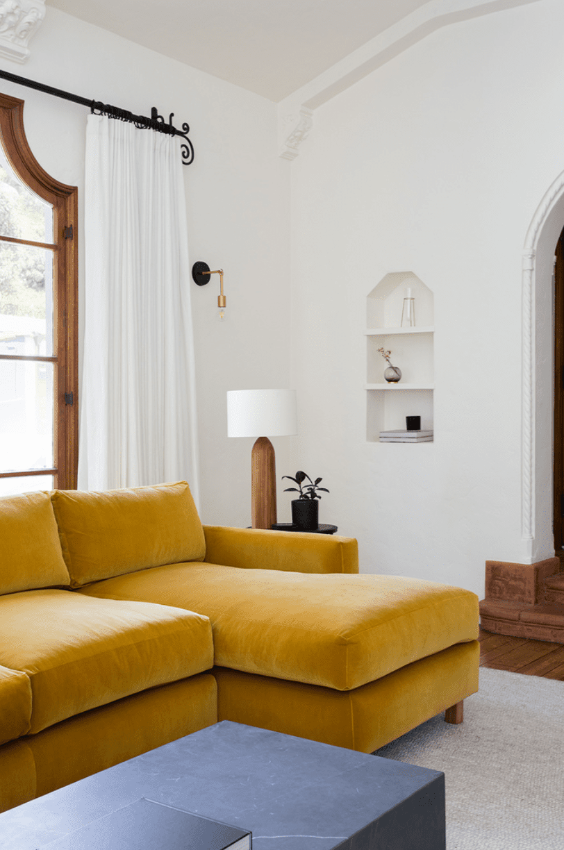 Living room with high ceilings, mustard yellow sectional, build in display shelves