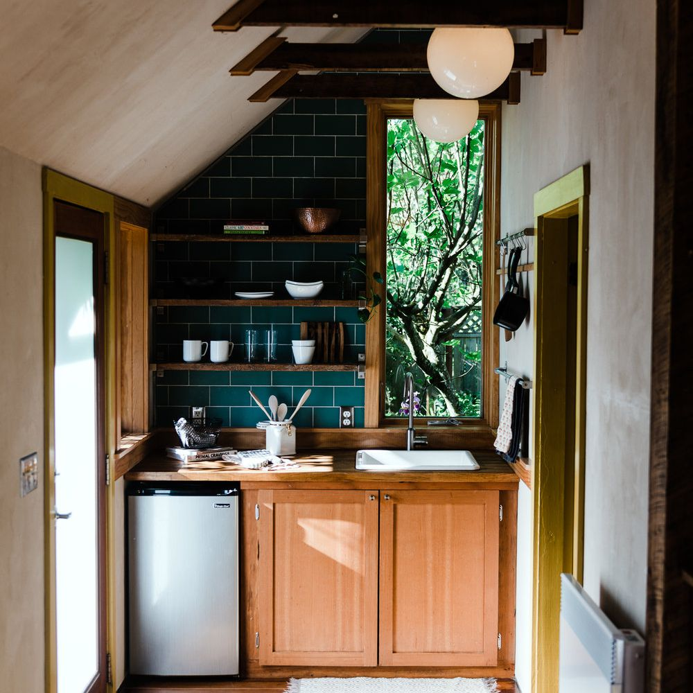 A small kitchenette with a backsplash lined with forest green tiles