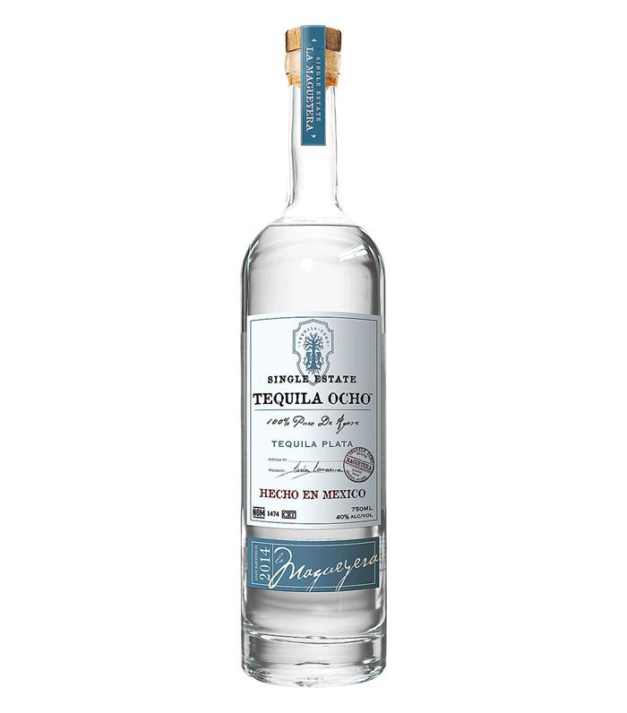 A clear bottle of Tequila Ocho Plata tequila with a blue and white label and cork.