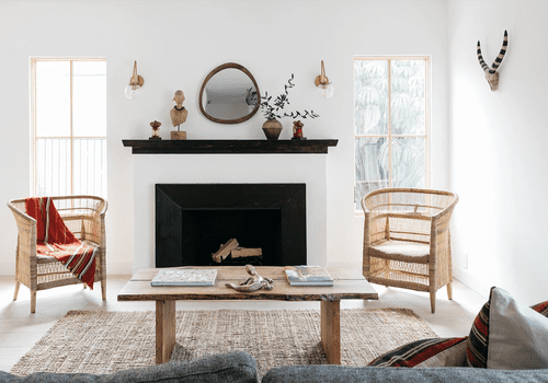 A living room with a fireplace, a wooden table, and two rattan chairs