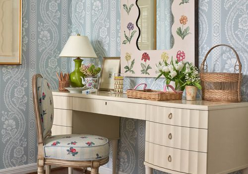 Floral vanity with antique wallpaper behind it.