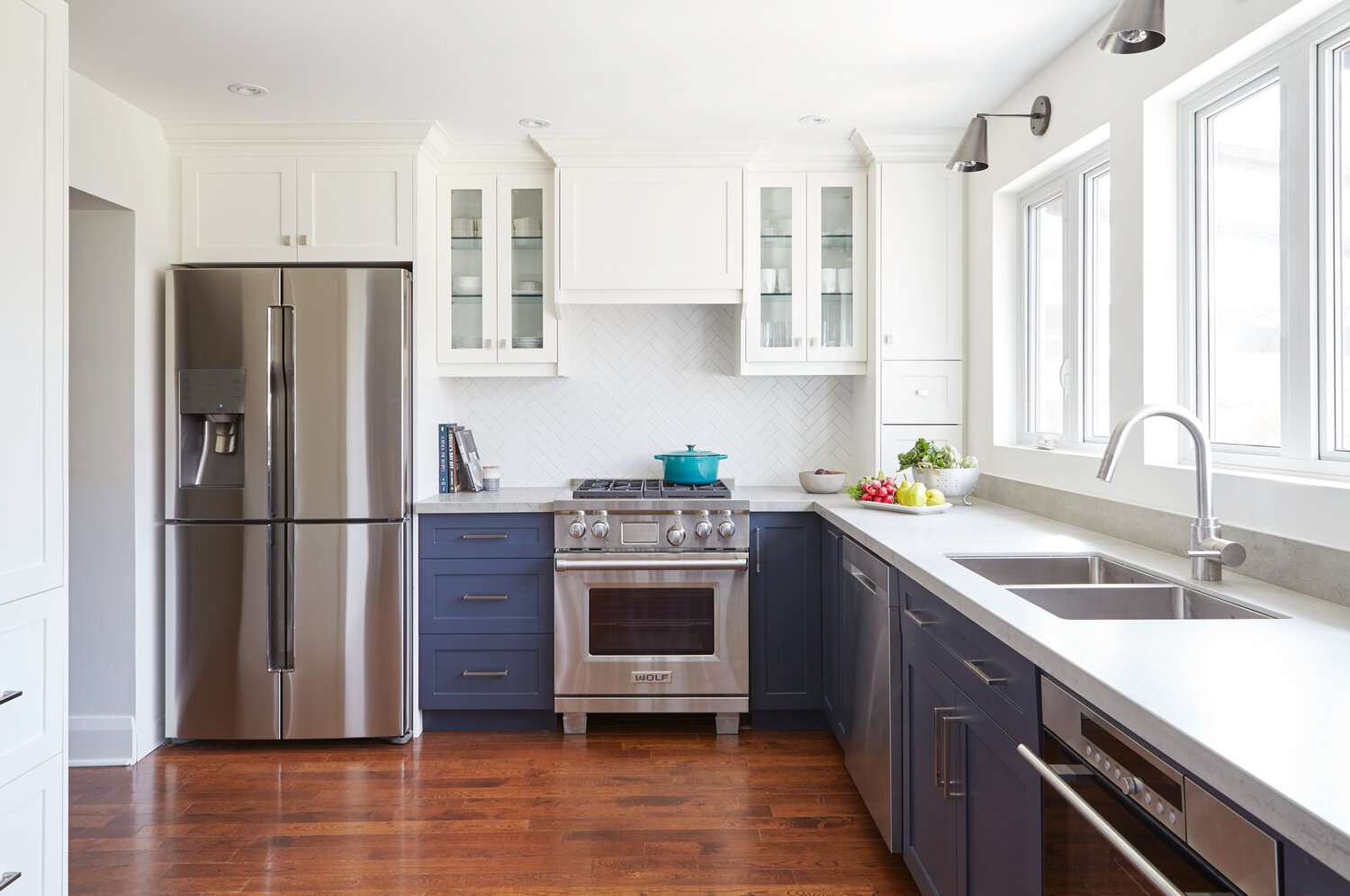 Minimalist kitchen with blue cabinetry, exposed dinnerware cabinets
