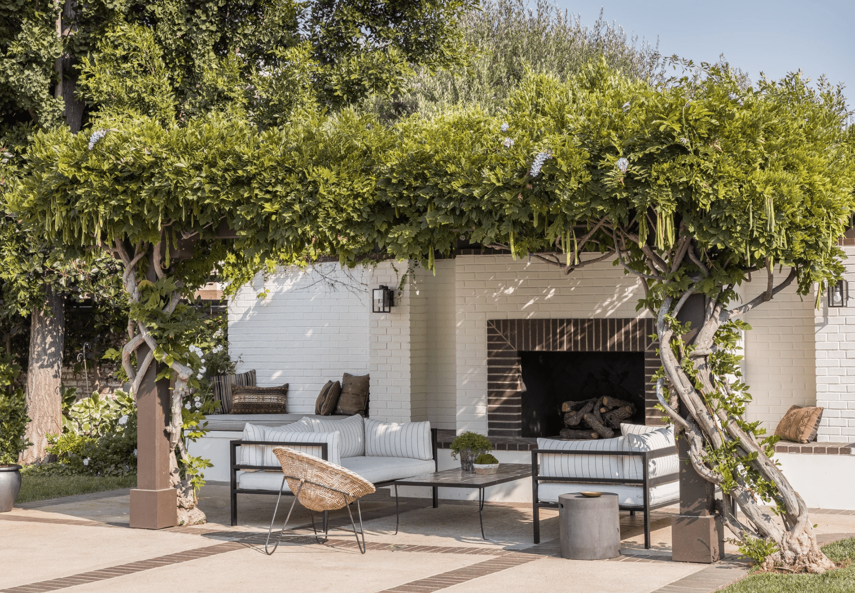 A brick-lined outdoor fireplace with sconces mounted on either side of the fire