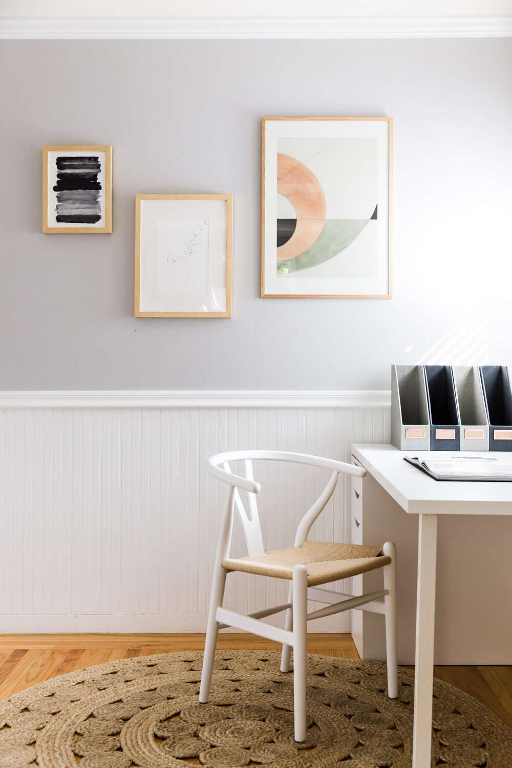 history of wishbone chair - white chair with tan seat in front of desk