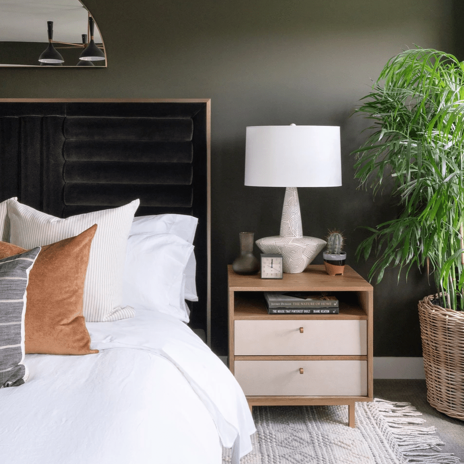 A bedroom with dark olive green walls