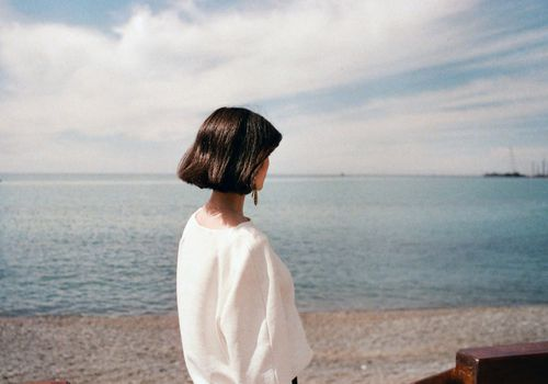 una mujer mirando hacia el océano
