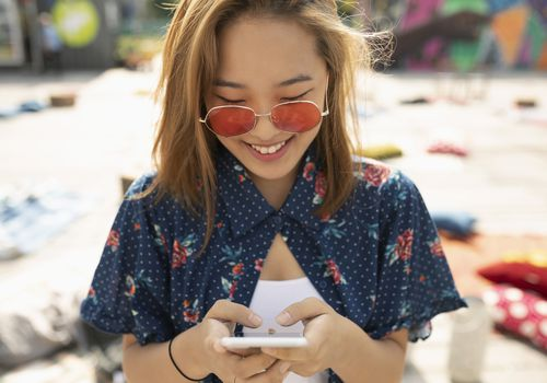 Young woman in sunglasses texting.