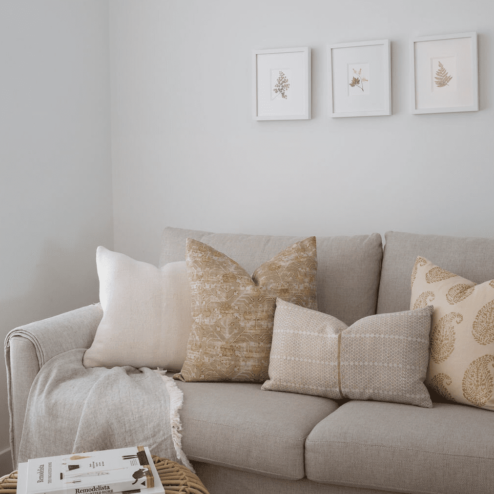 A living room with a beige couch that's topped with beige and gold printed throw pillows