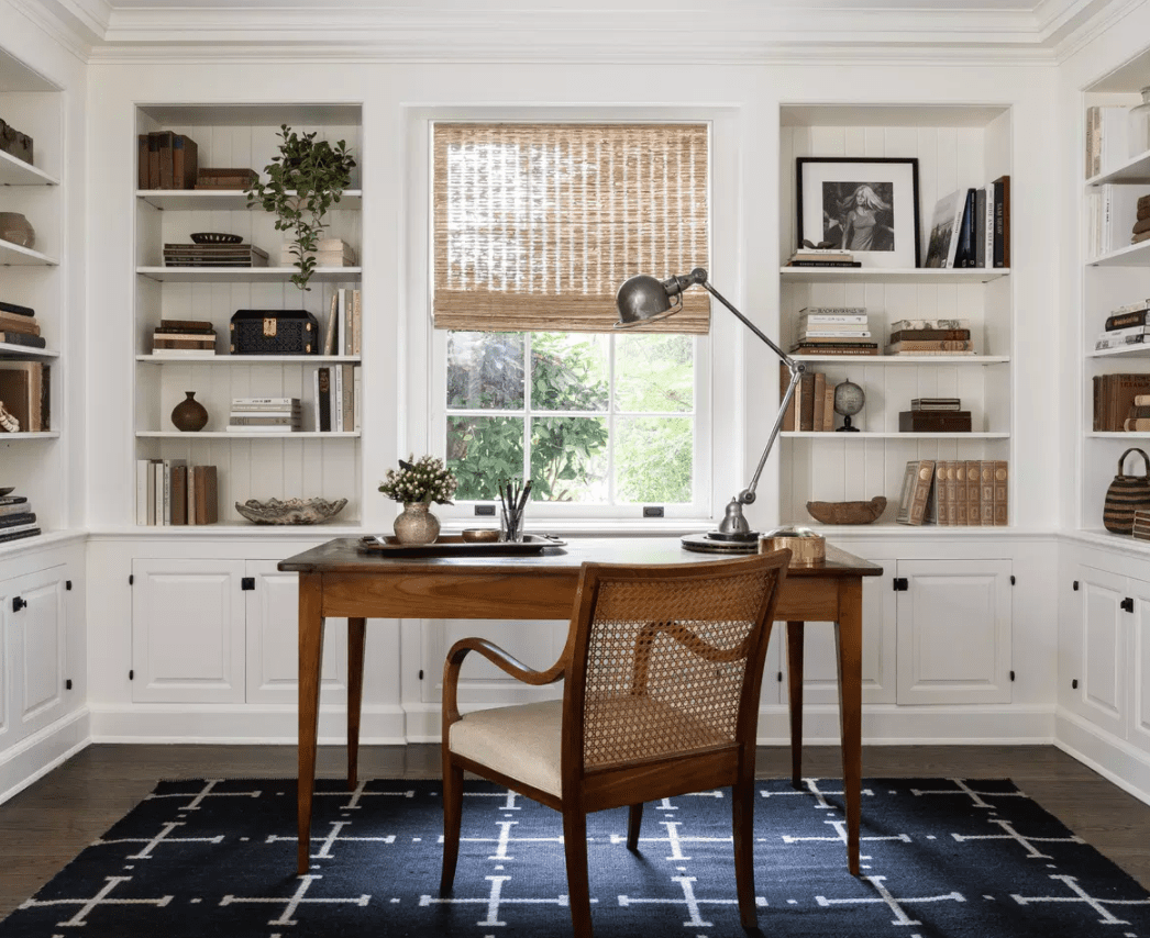 A home office with a dark blue rug and several modern coastal accents