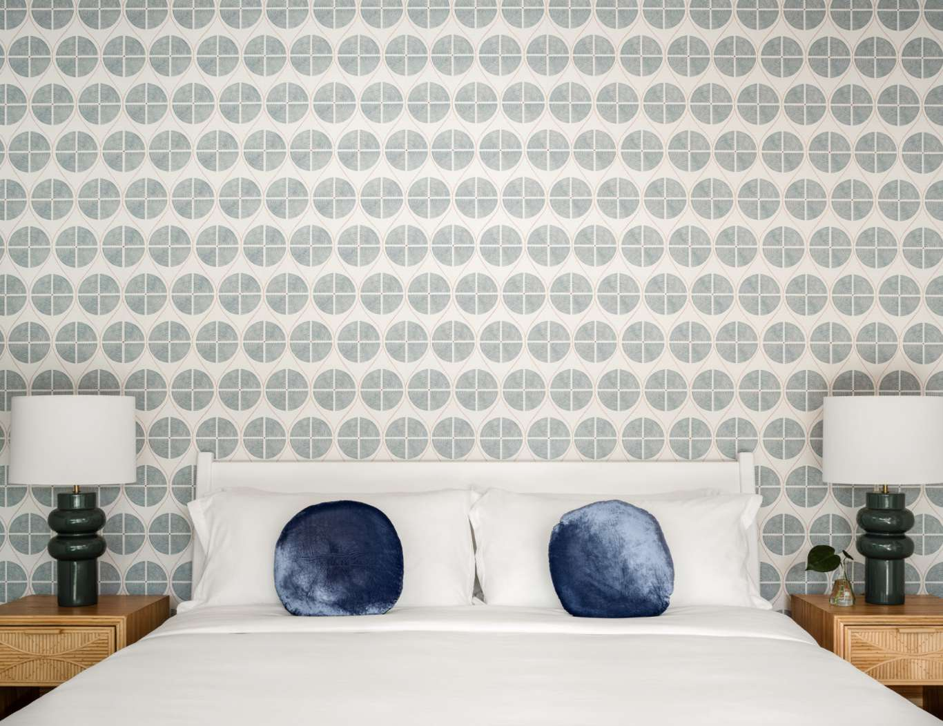 bedroom with circular pattern wallpaper and circle throw pillows on bed