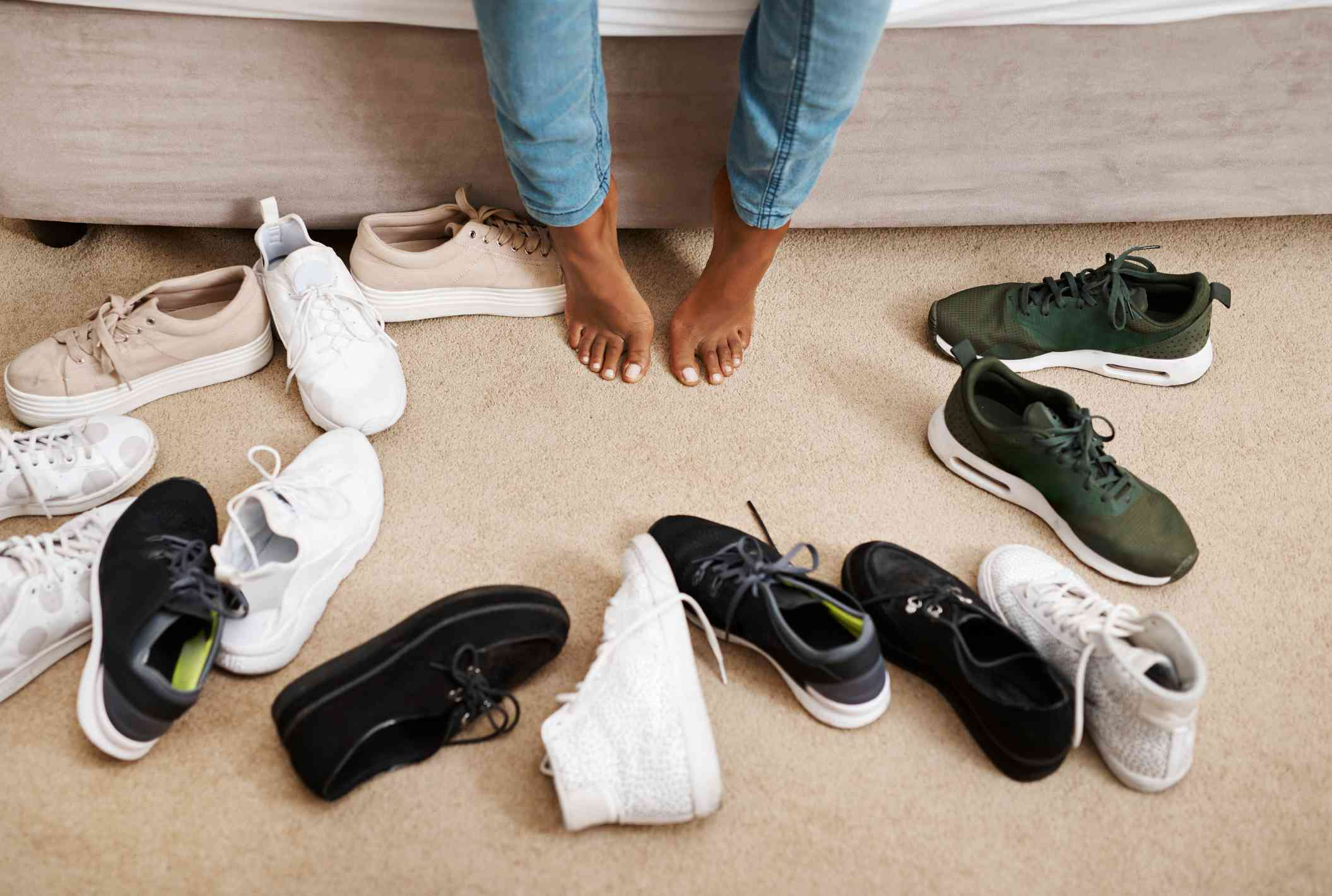 Close up shot of woman's feet surrounded by several pairs of sneakers
