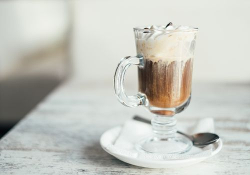 Coffee cocktail in a glass mug, with a large dollop of cream.
