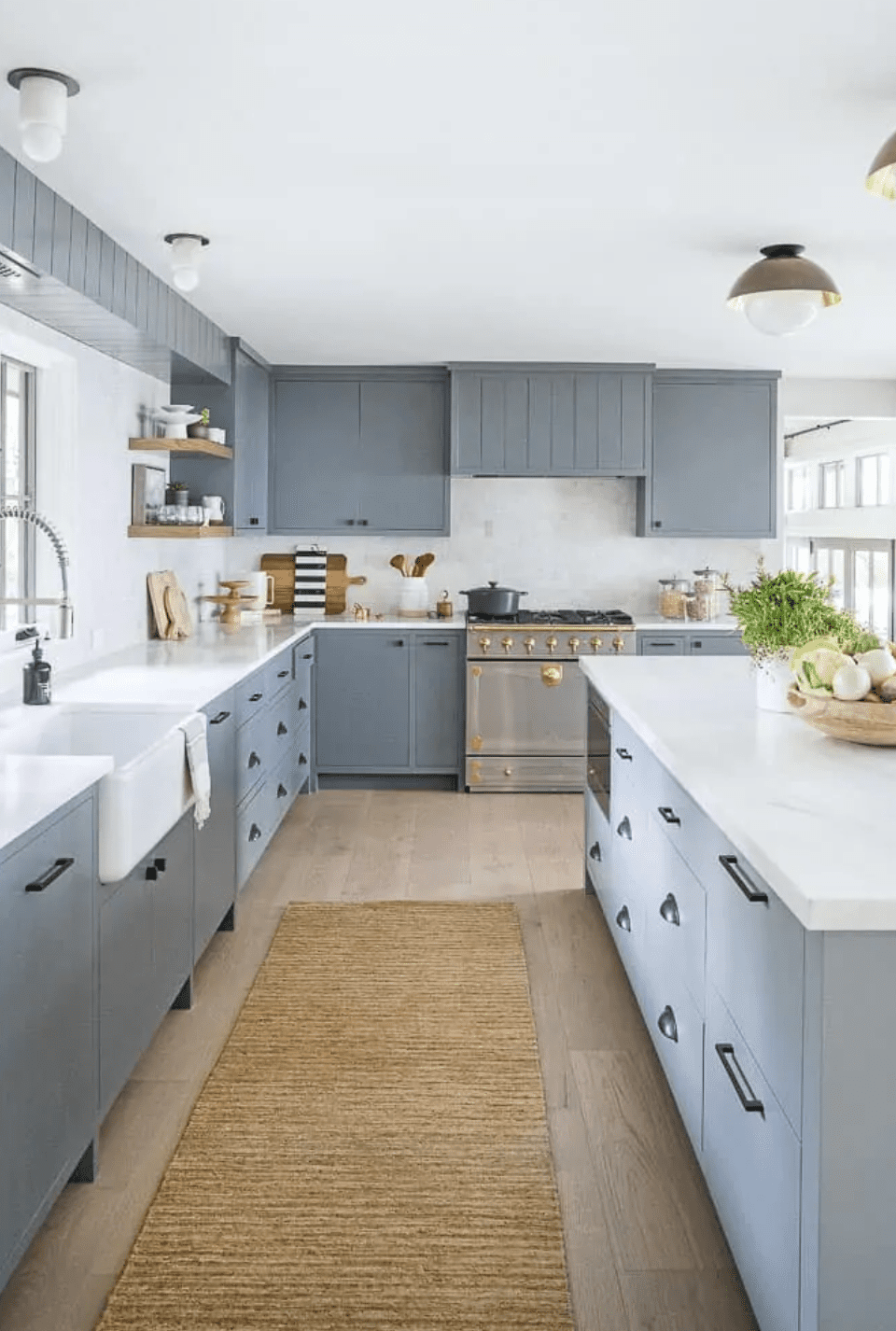 A kitchen with gray cabinets and a jute rug on the floor