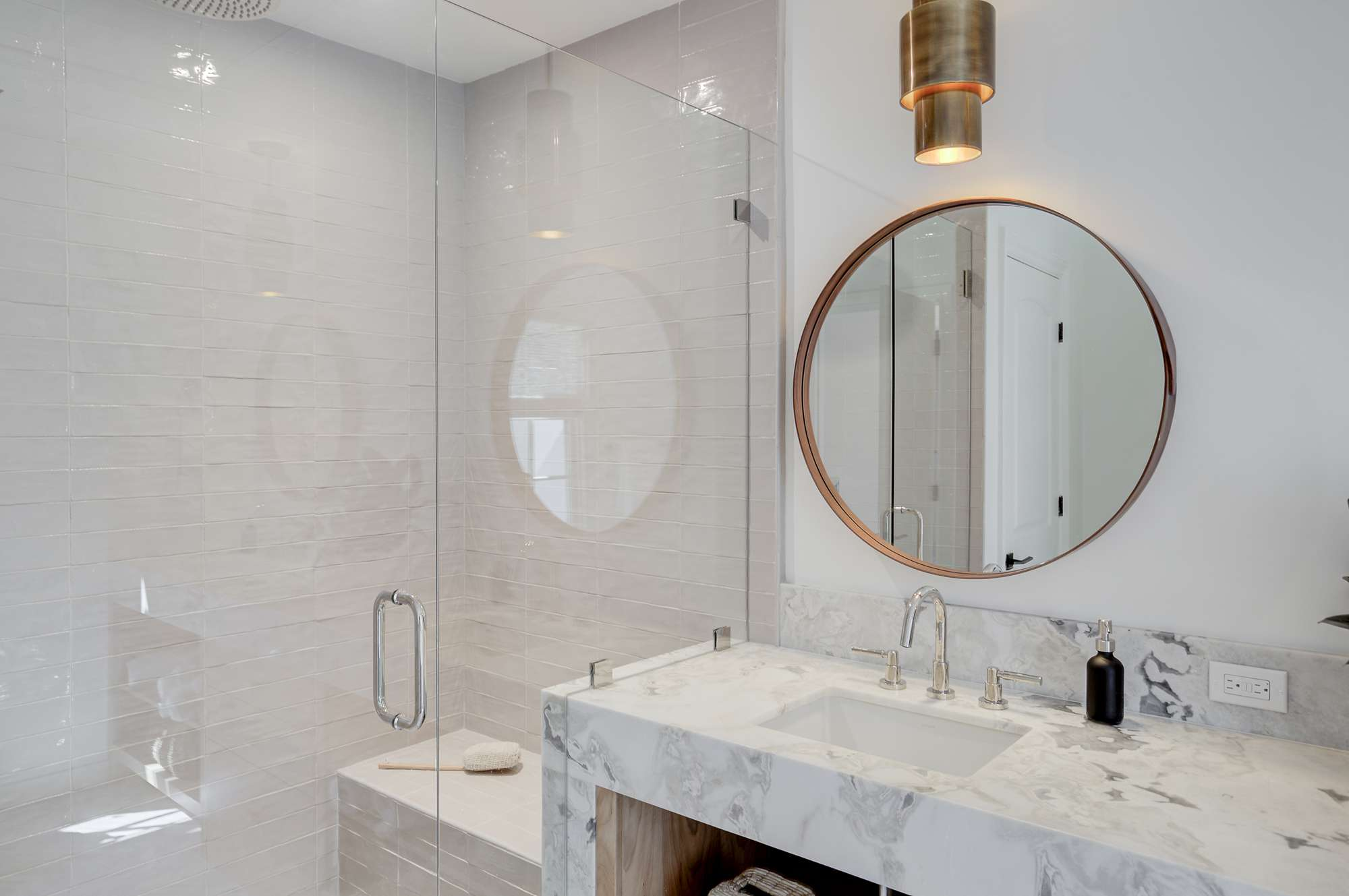 Vanity with marble countertop and glass shower stall.