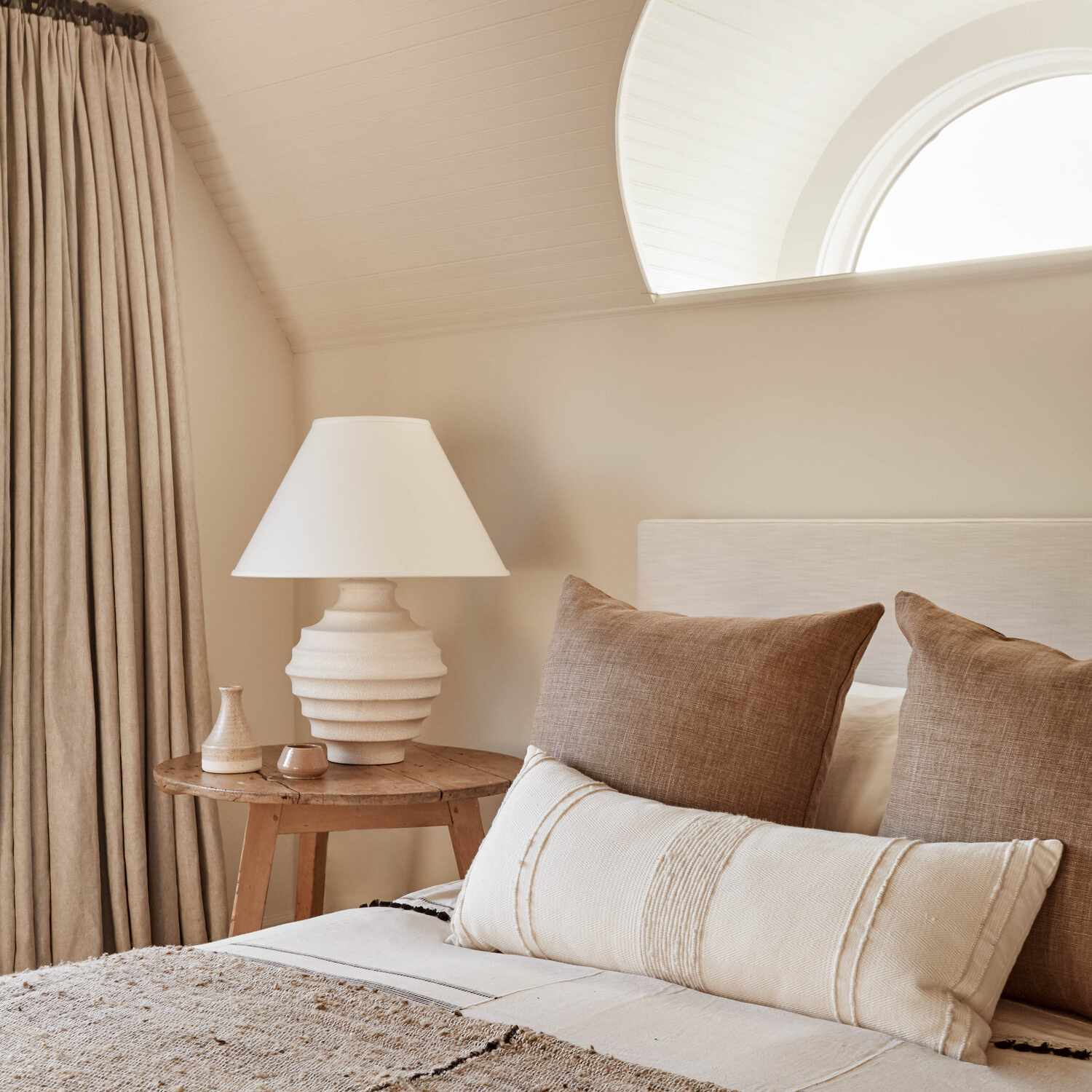 A bedroom decorated with a monochromatic almond palette that extends from ceiling to floor