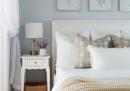 Spring inspired bedroom with floral wall art and soft bed linens.