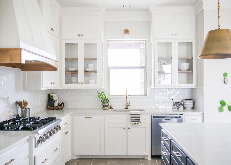 Bright white kitchen with stainless steel dishwasher.