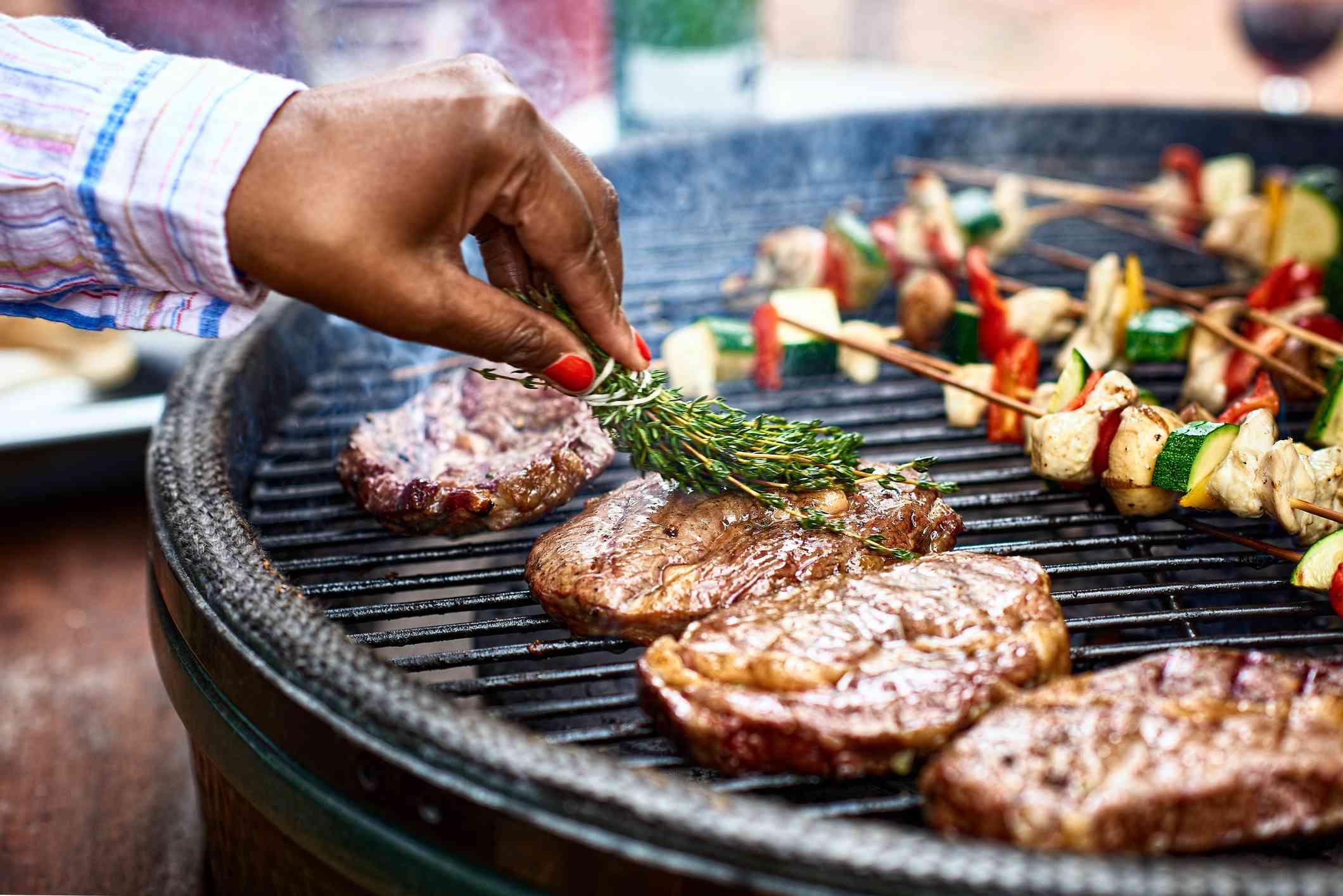 Woman's hand seasons steaks on a grill