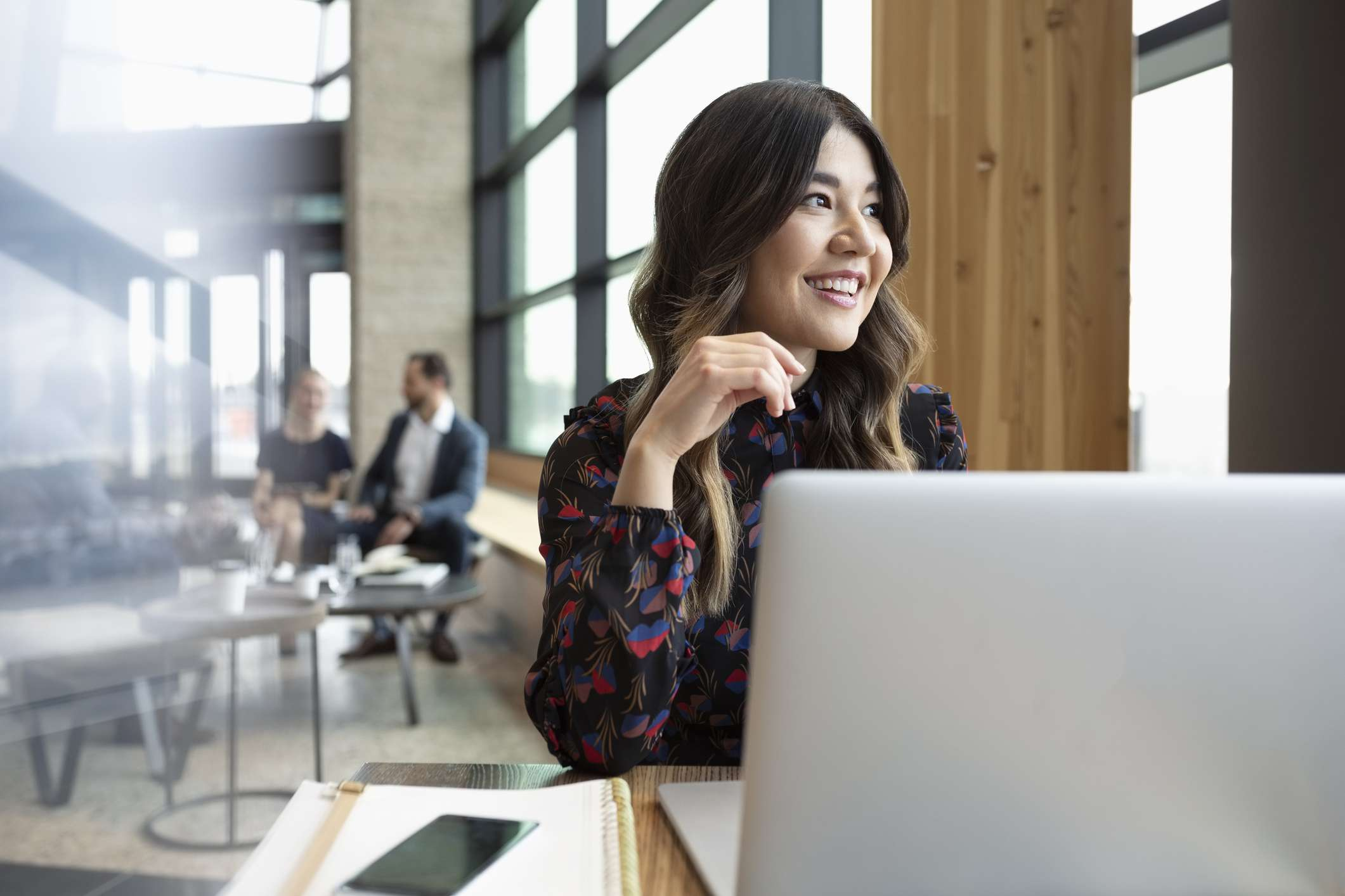 Woman in front of laptop looks into the distance, smiling.