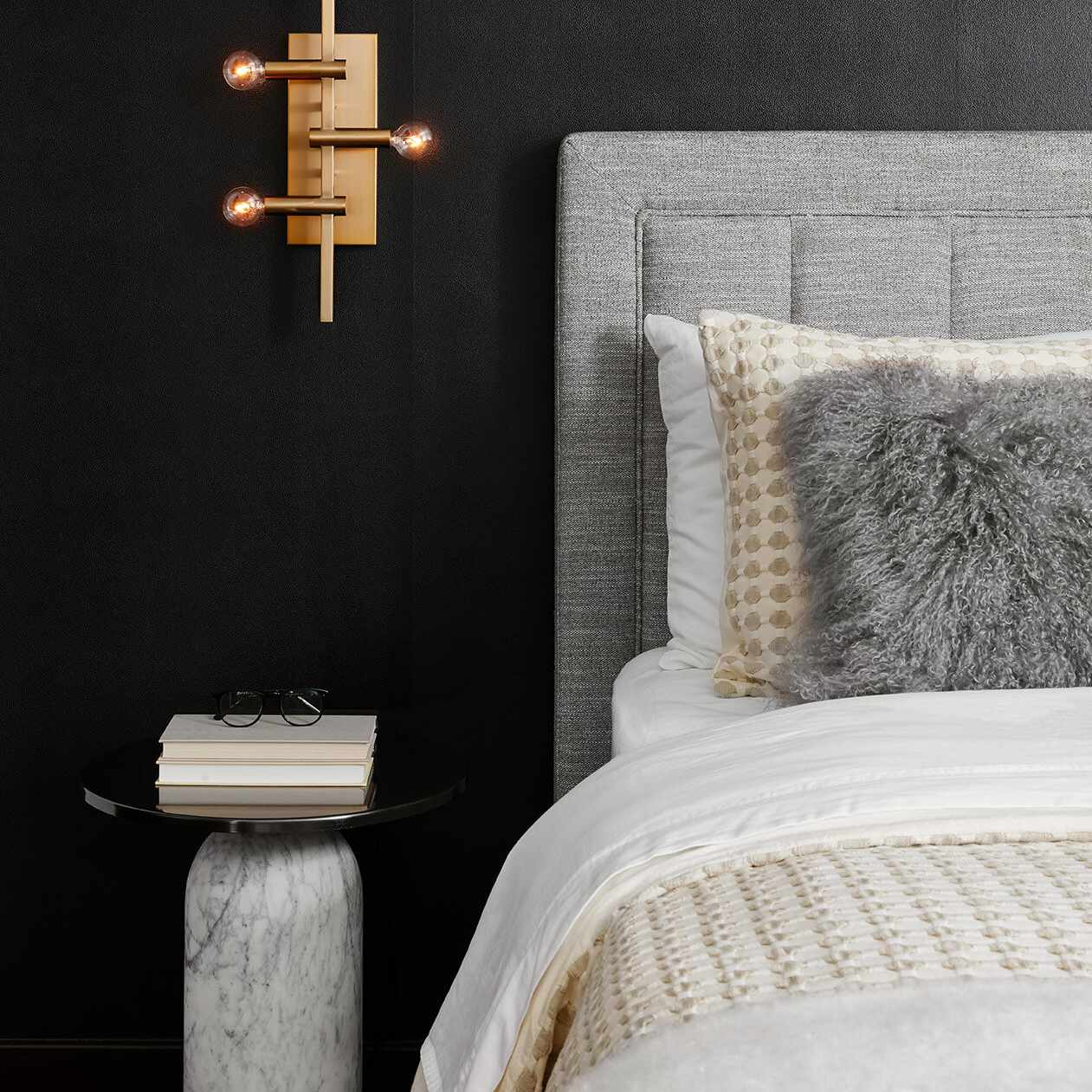 A luxe modern bedroom with a modern gold sconce