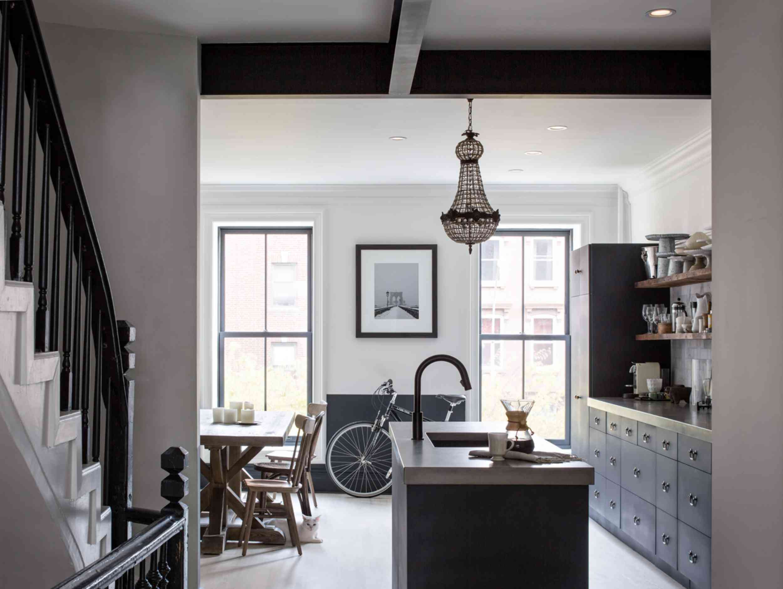 A navy and white kitchen with black windows, black ceiling beams, and black hardware