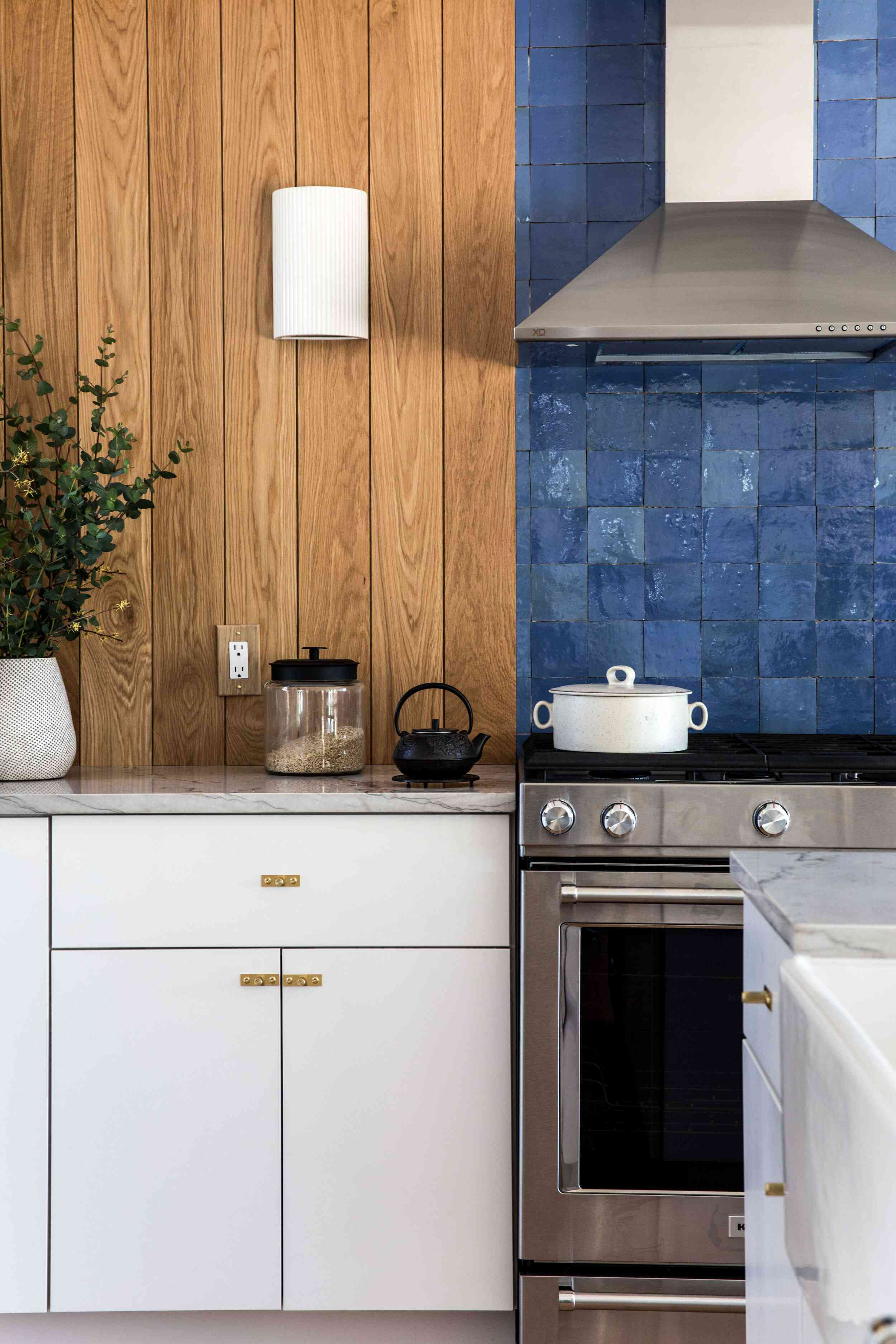 A kitchen with wood-lined walls and a blue tiled backsplash