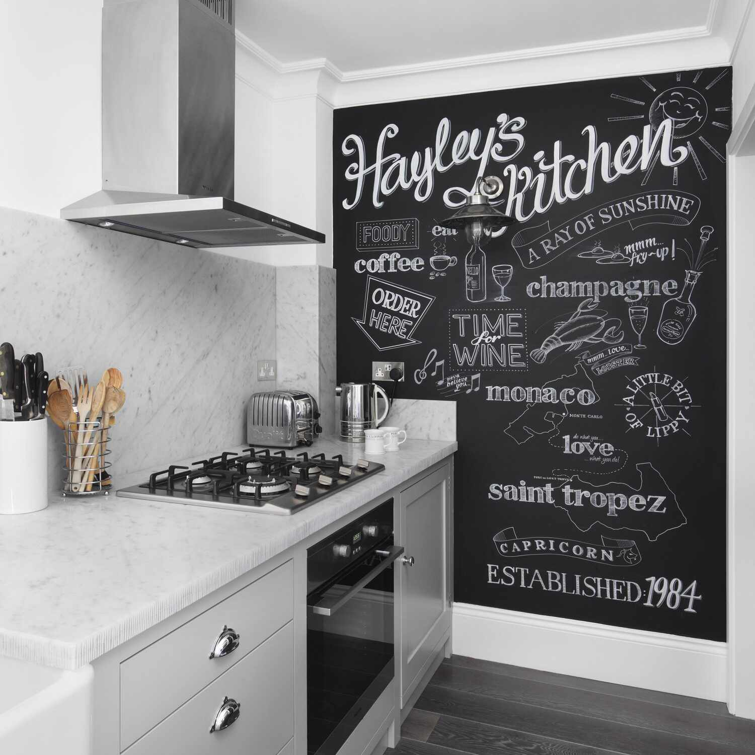 A kitchen with light gray cabinets, marble countertops, and charcoal floors
