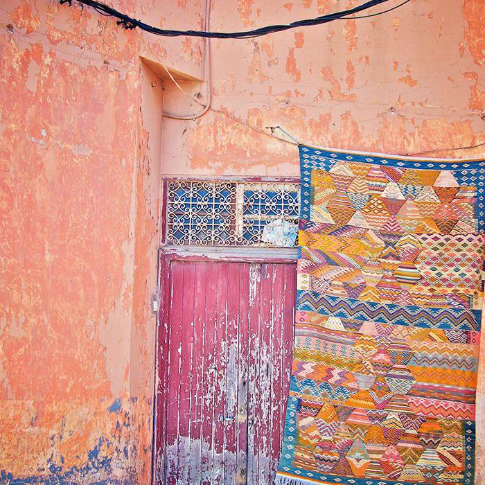 a colorful rug hanging against a distressed, colorful building