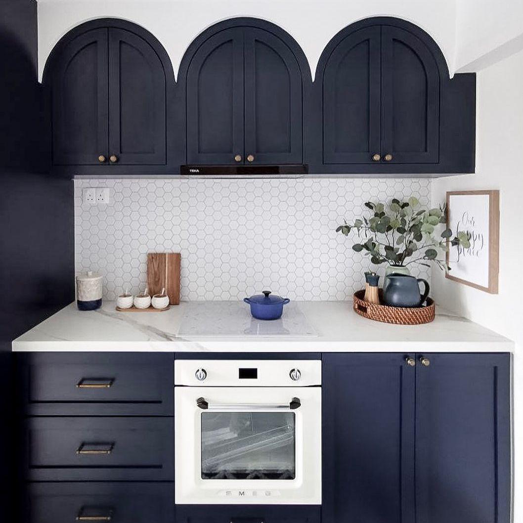 Blue arched kitchen cabinets with penny tile backsplash.