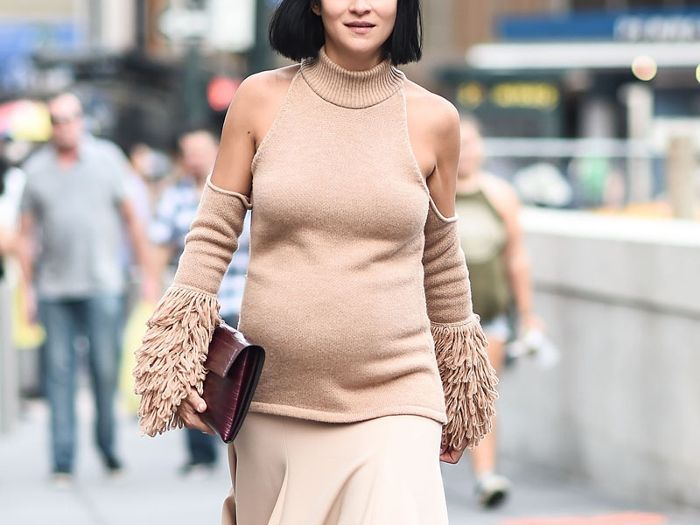 A pregnant woman wearing a cold shoulder sweater with fringed sleeves.