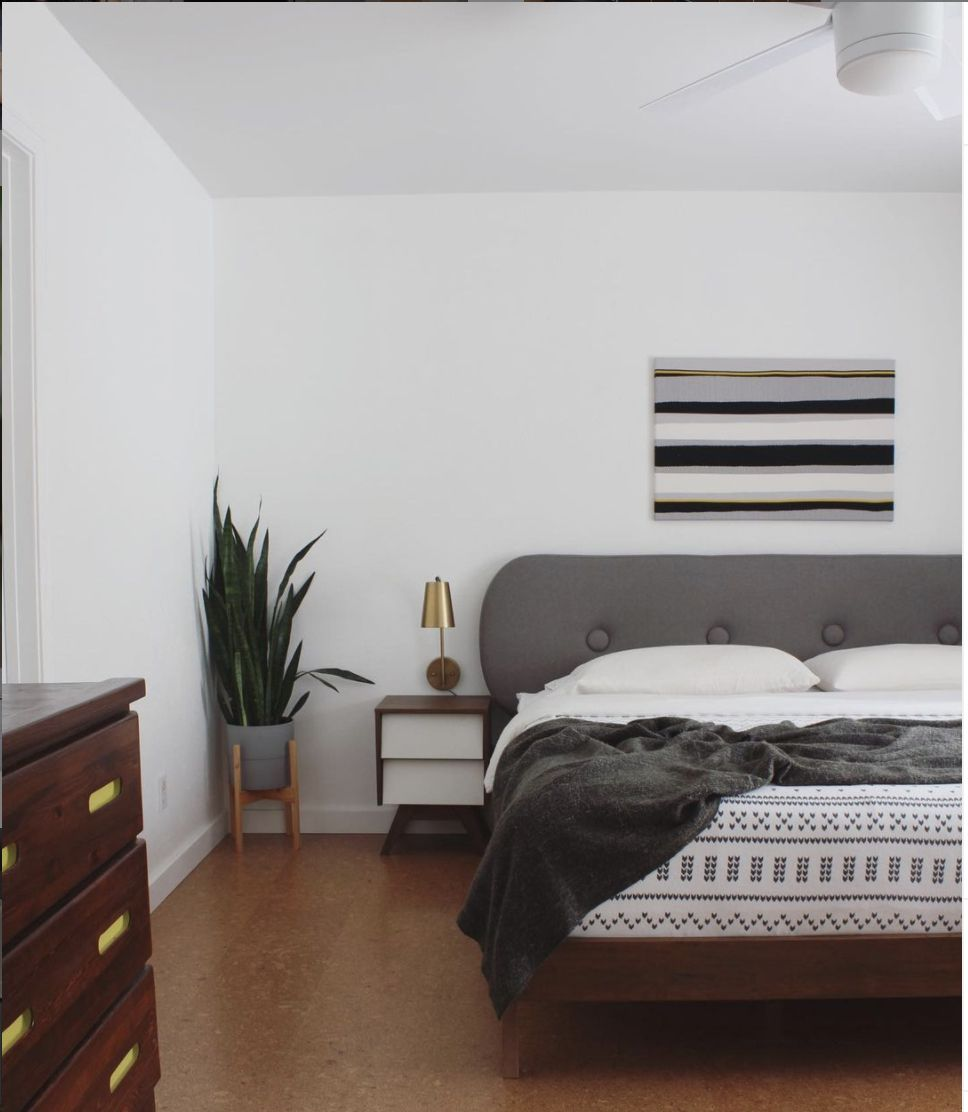 bedroom with white walls, modern color scheme, golden sconce