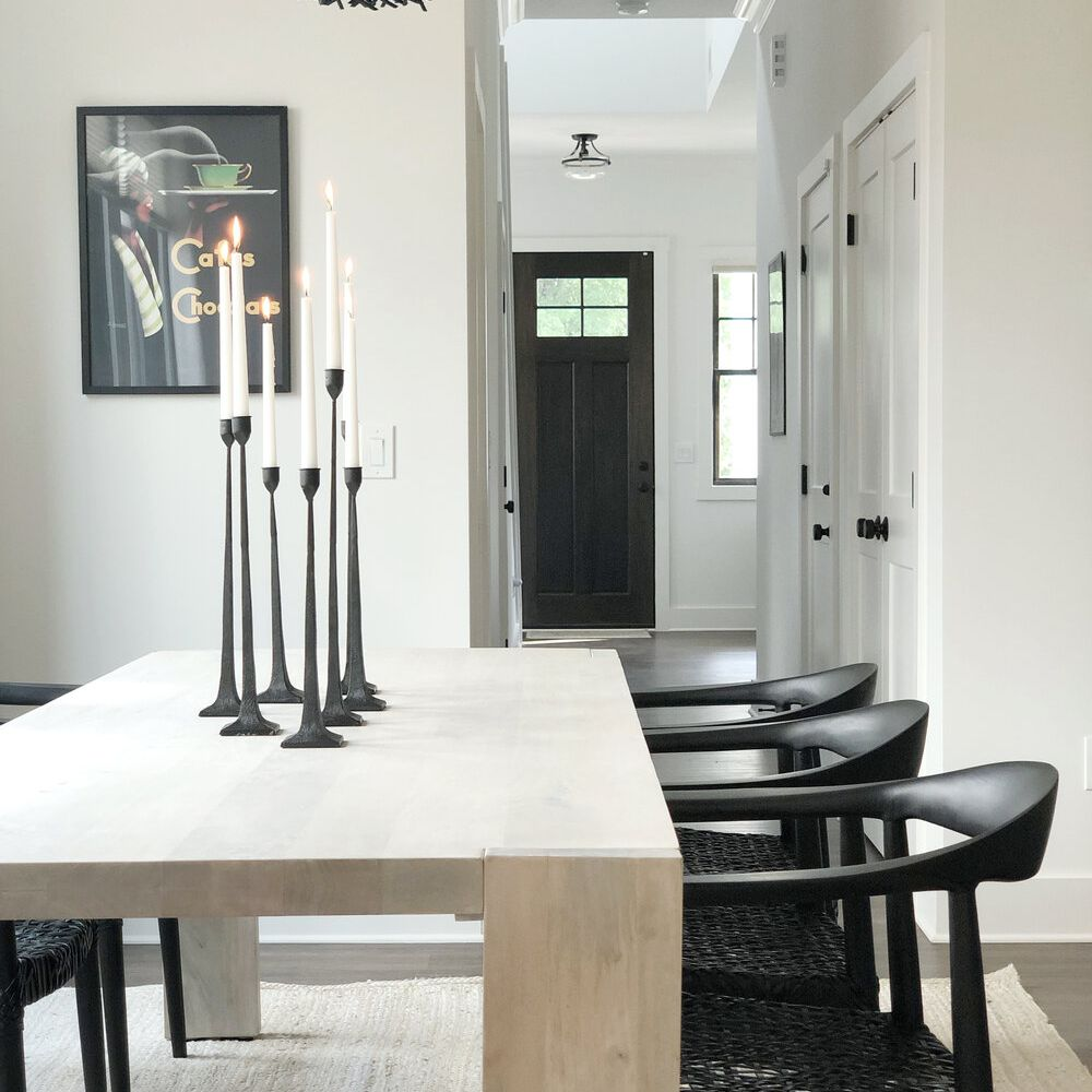 A modern dining room table topped with a cluster of black candlesticks
